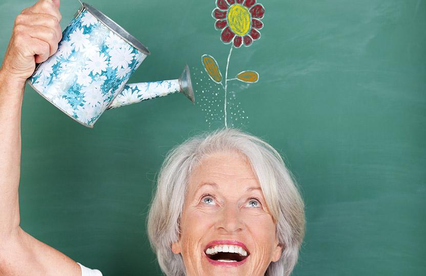 Lächelnde Seniorin gießt symbolisch eine auf eine Tafel gemalte Blume über ihrem Kopf