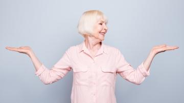 Eine ältere Dame steht im Raum und macht eine sportliche Übung mit den Armen.