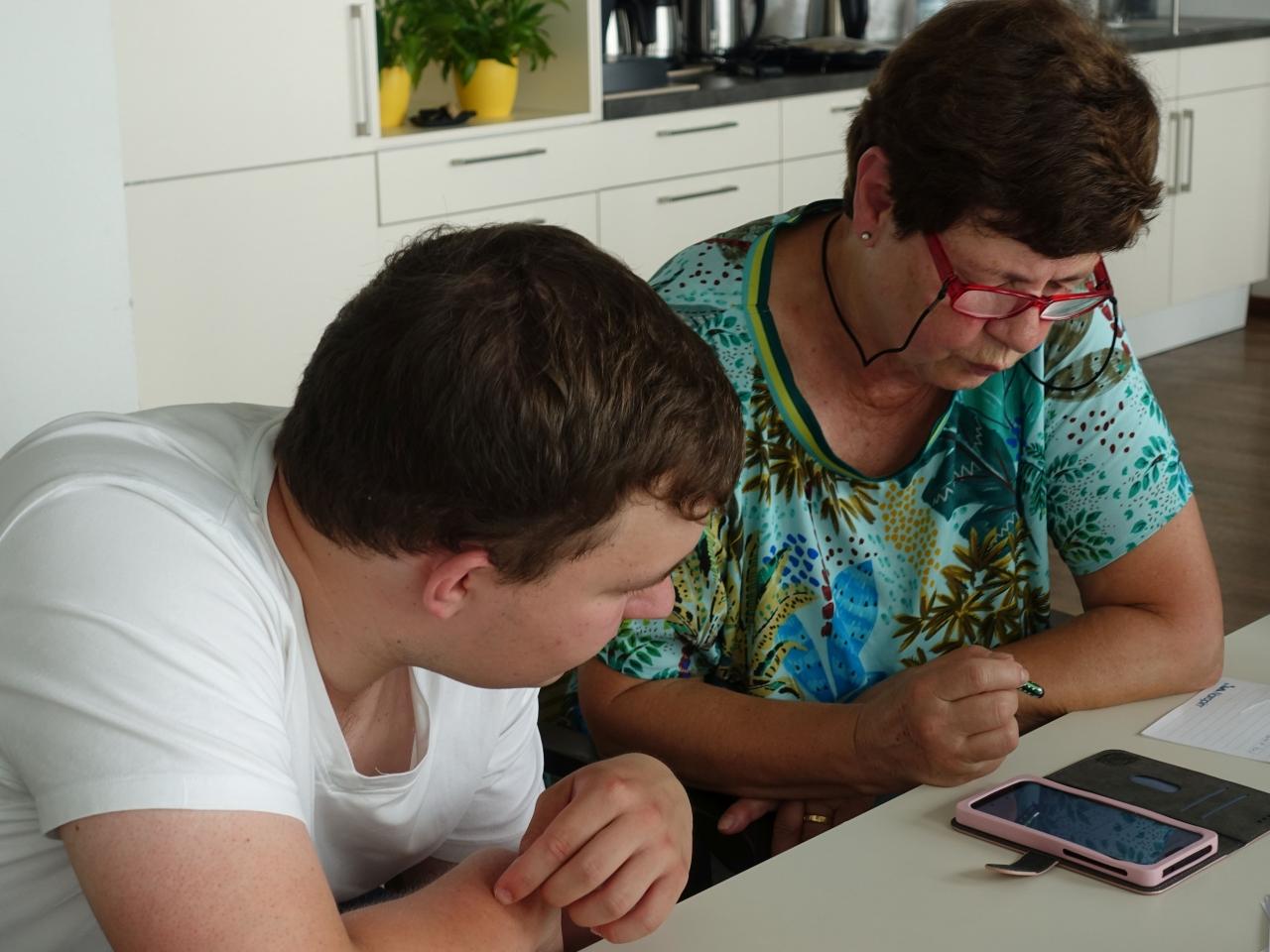 Ein Smartphone Pate und eine ältere Dame schauen auf ein Smartphone.
