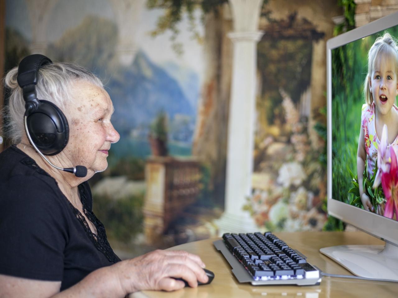 Eine ältere Frau sitzt mit einem Kopfhörer vor einem Bildschirm auf dem ihre Enkeltochter zu sehen ist.