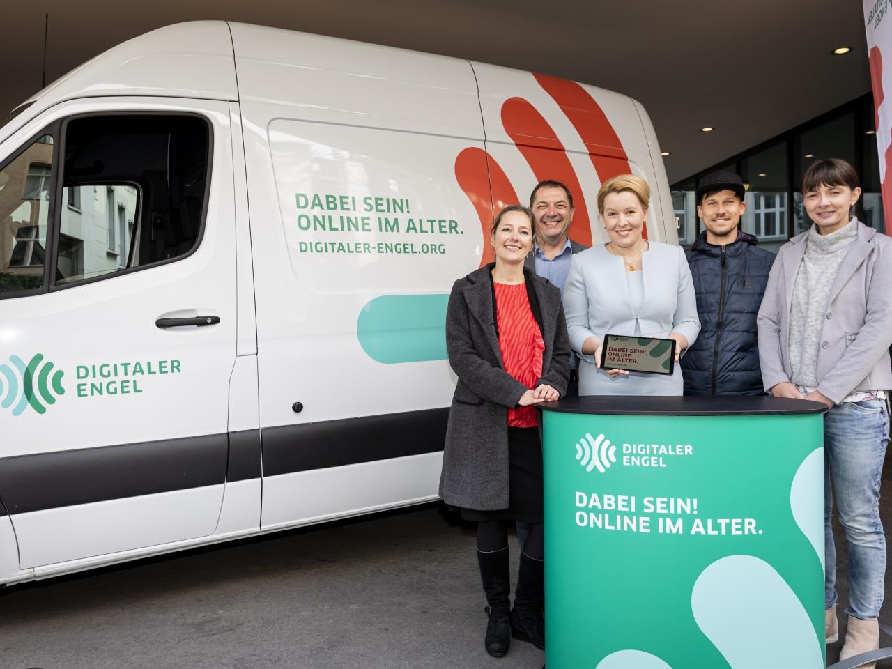 """Familienministerin Giffey steht mit dem Expertenteam vor einem weißen Van, dem """"Digitalen Engel"""""""