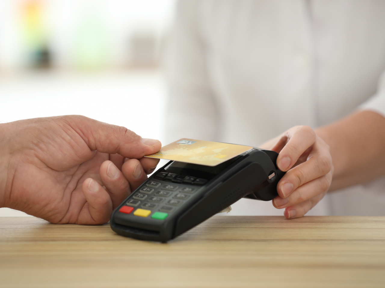 Jemand hält seine Geldkarte kontaktlos an ein Bezahlgerät
