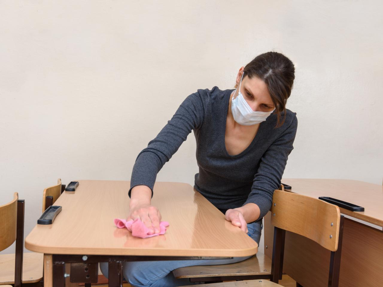 Frau desinfiziert Schreibtisch und trägt dabei eine Maske