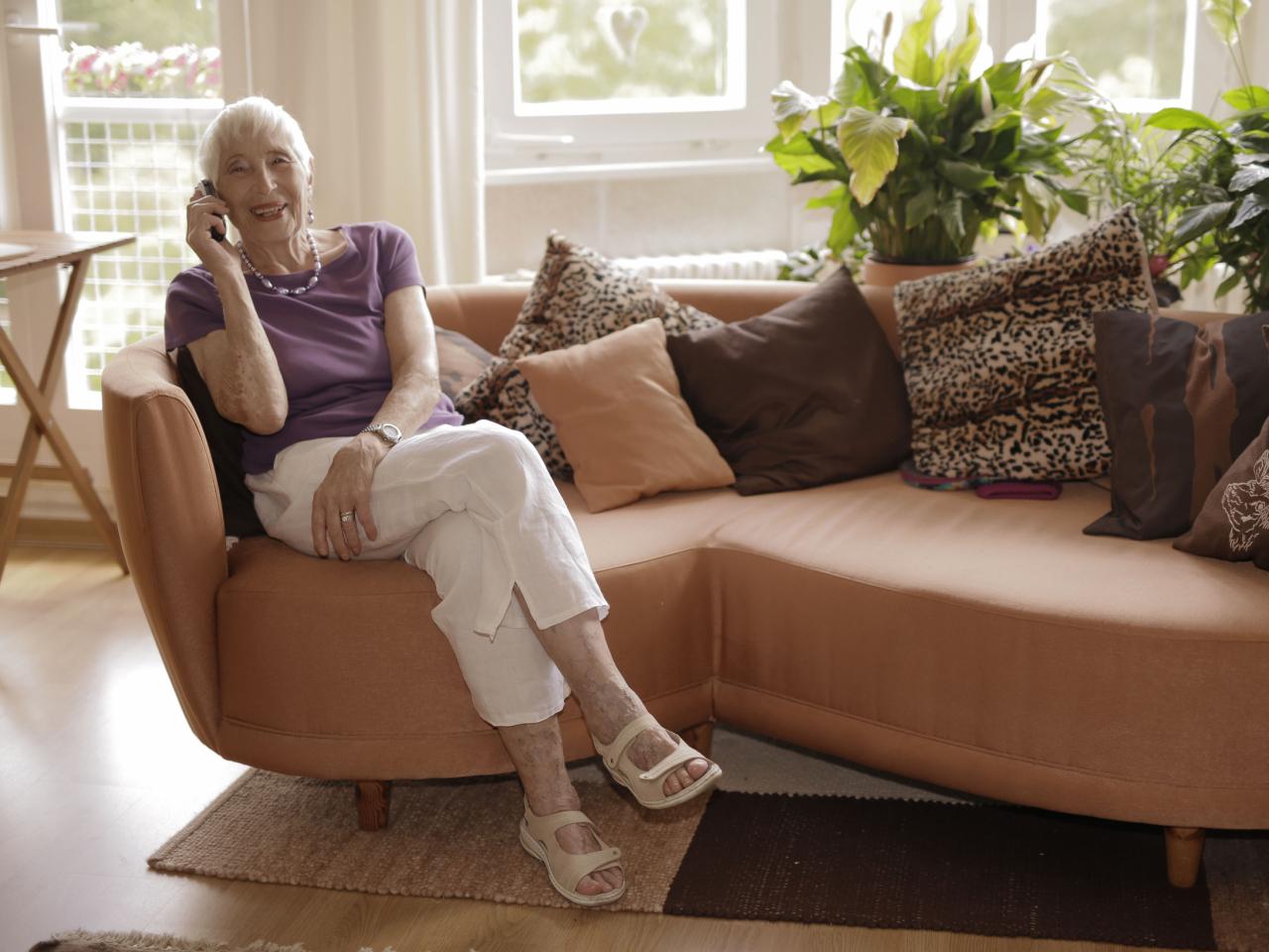 Frau sitzt auf Couch und telefoniert