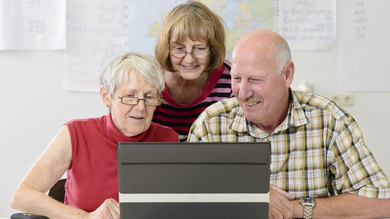 Drei ältere Menschen schauen gutgelaunt auf ein Notebook