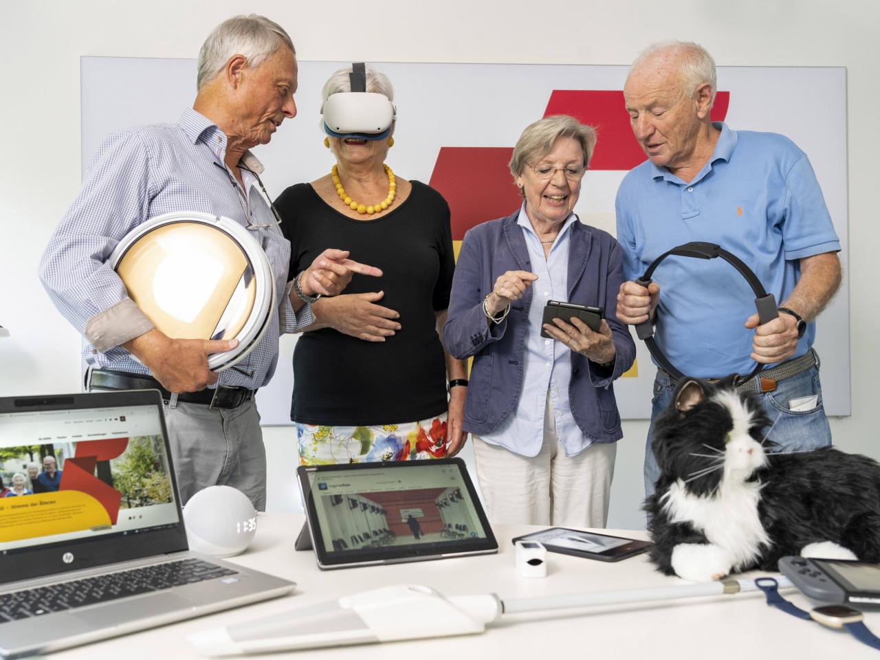 Vier ältere Menschen testen verschiedene digitale Geräte
