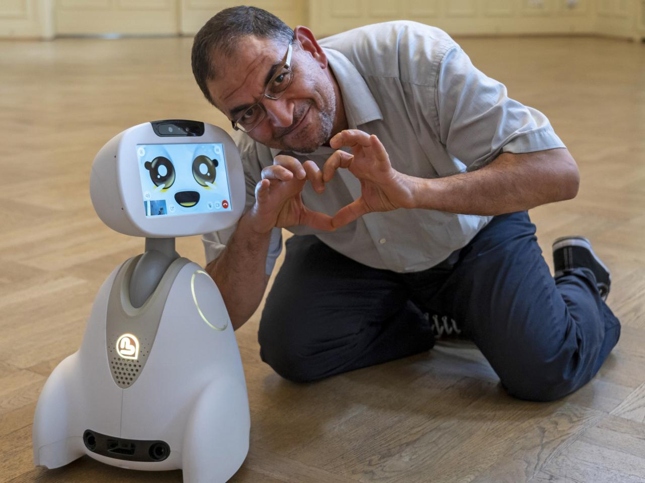 Mann hockt neben einem Roboter und formt mit den Händen ein Herz